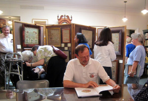Needlework authority and dealer Stephen Huber perusing the book during the signing and sampler exhibit.